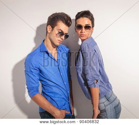 Young fashion couple posing together againt a grey wall. The man is leaning on the wall while looking down and the woman is looking at the camera while holding both hand in the pockets.