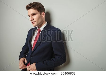 Portrait of a handsome business man leaning on a wall while closing his jacket.