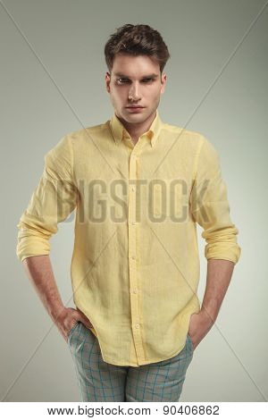 Serious young fashion man standing with his hands in pockets while looking at the camera.