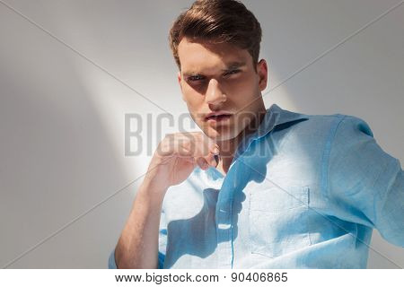Arrogant young casual man looking at the camera, on grey studio background,