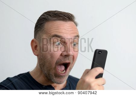 Surprised Man Looking At His Mobile Phone
