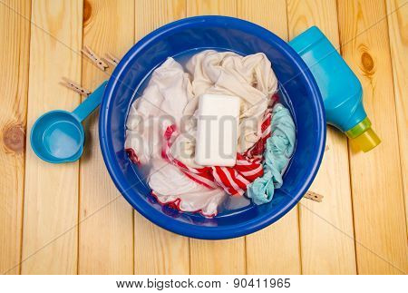 Dirty laundry in blue bowl with soap