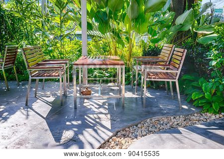 A Wooden Table Set In Lush Garden Setting