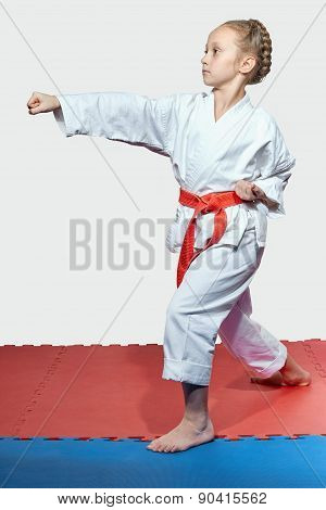 Girl with red belt in the rack of karate is beating blow arm