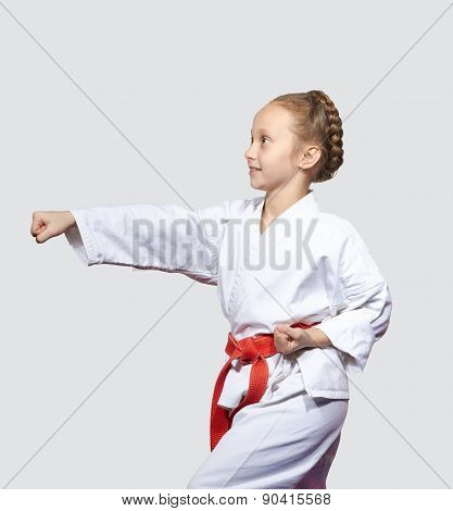 On a light background small sportswoman is doing blow hand