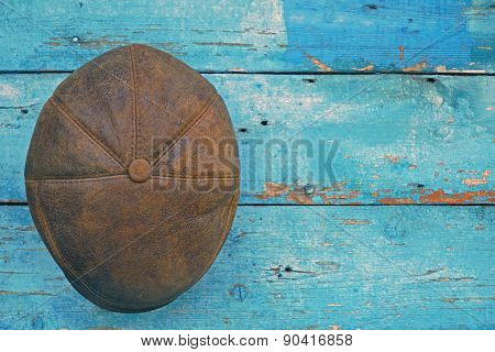 leather brown hat on wooden background