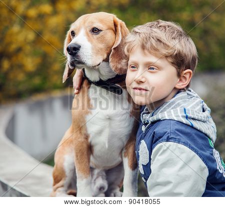 Little boy and his beagle sitting outside