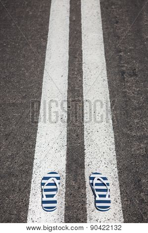 slippers with stipes lying on asphalt close up