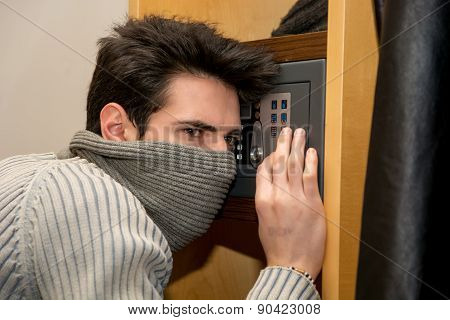 Young male burglar opening a small home vault or safe