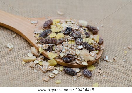 Oat Flakes In Wooden Spoon On Sackcloth Background