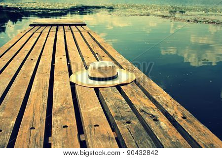Straw hat on a wooden lake bridge