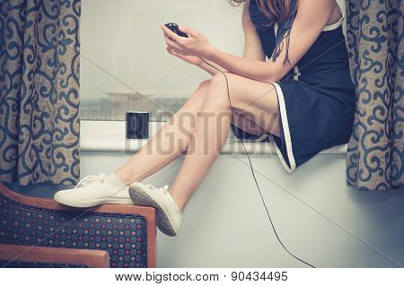 Woman Charging Her Phone By Window