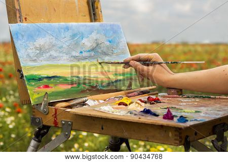 The artist in the meadows painting landscape oil paints on canvas from nature.
