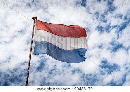 Dutch Flag Against A Cloudy Sky