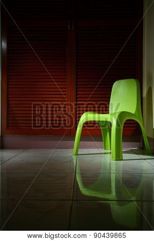 Green plastic chair in a room