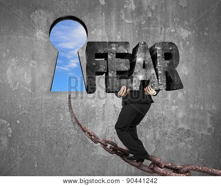 Man Carrying Fear Word On Chain Toward Keyhole With Sky