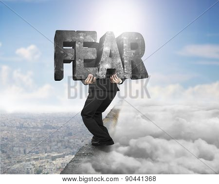 Man Carrying Fear Concrete Word On Ridge With Cloudscape Cityscape