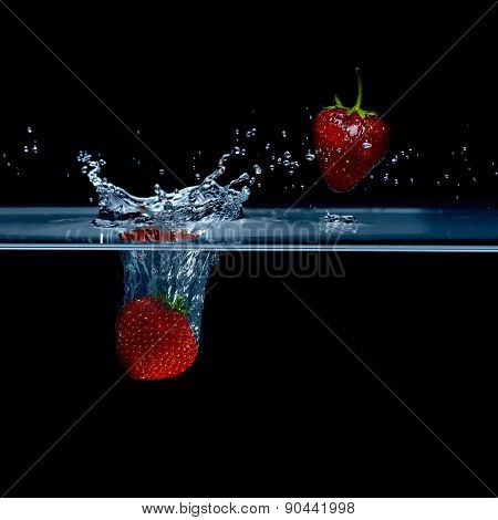 Strawberry falls into water. Strawberries in the air. Splash water.