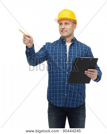 repair, building, construction and maintenance concept - smiling man or builder in helmet with clipboard pointing pencil