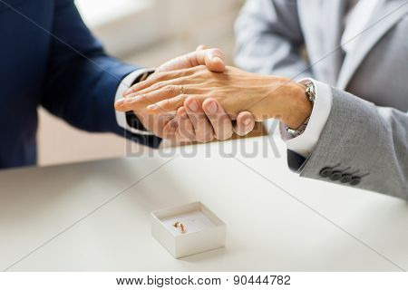 people, homosexuality, same-sex marriage and love concept - close up of happy male gay couple hands with wedding ring on and little box on table