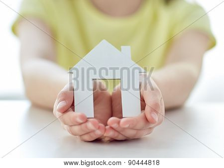 people, charity, family and home concept - close up of happy girl holding paper house cutout in cupped hands