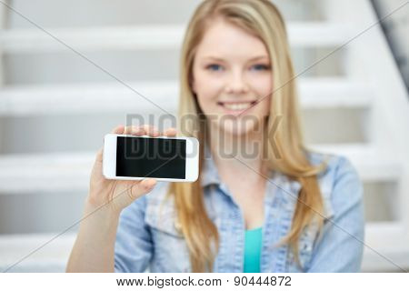 people, technology and internet, adverticement concept - close up of happy teenage girl showing smartphone blank screen