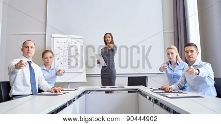 business, people and teamwork concept - group of businesspeople meeting and pointing finger at you in office
