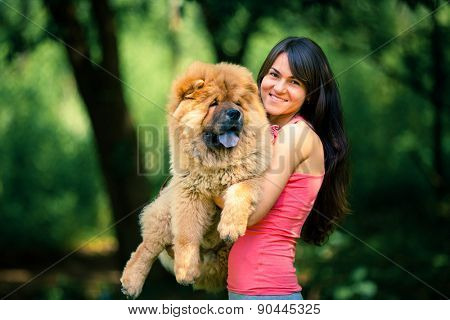girl holding a dog on a background of park