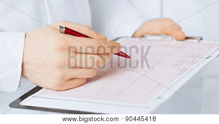 bright picture of male doctor hands holding cardiogram