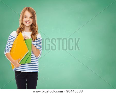 education, people, children and school concept - happy girl holding colorful folders over green board background