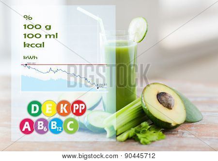healthy eating, organic food and diet concept - close up of fresh green vegetable juice glass and vegetables on table with calories and vitamin chart