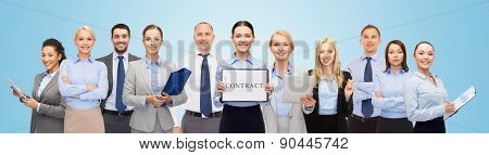 business, people, partnership, work and office concept - group of happy businesspeople holding contract over blue background
