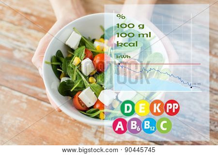 healthy eating, dieting, food and people concept - close up of woman hands showing salad bowl with calories and vitamin chart