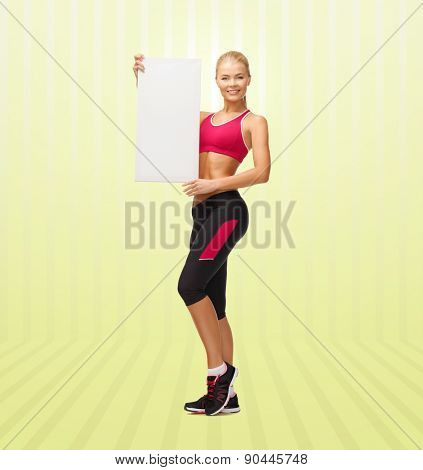 sport, fitness, people and advertisement concept - happy smiling sportswoman with white blank board over yellow striped background