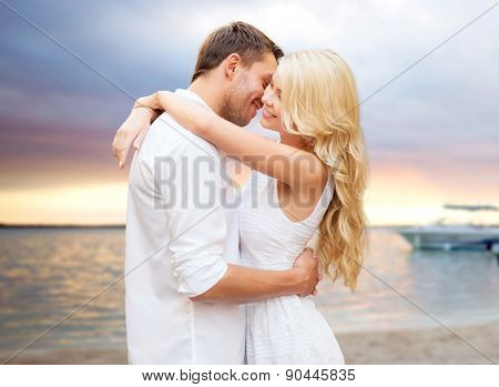 summer holidays, people, love and dating concept - happy couple hugging over sunset at summer beach background