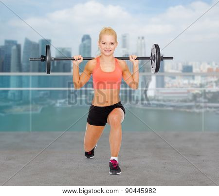 fitness, sport, weightlifting and people concept - sporty woman exercising with barbell over city waterside background