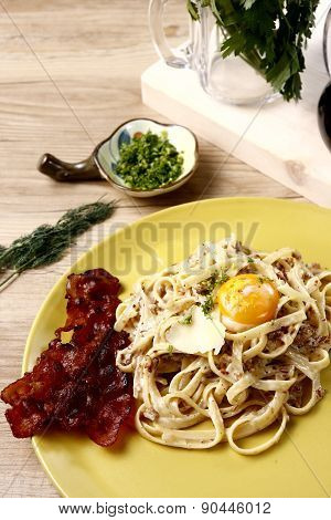 Linguine pasta on white sauce with egg and bacon