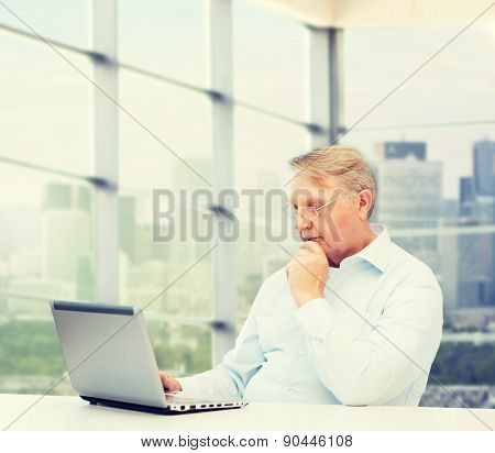 technology, oldness and people concept - senior man in eyeglasses with laptop over office window background