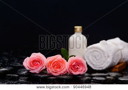 Three rose and towel with massage oil and therapy stones