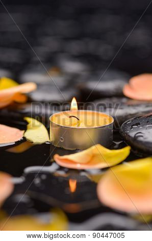 rose petals with candle and therapy stones