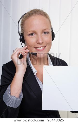 a friendly young woman with headset in customer service on the phone with a customer. friendly hotline employee.