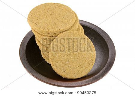A dish of gluten free crumbly rough Oatcakes, isolated on white background