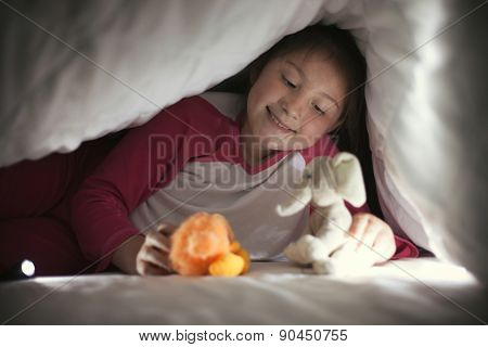 Girl under sheet playing with toys using flashlight, happy and smile