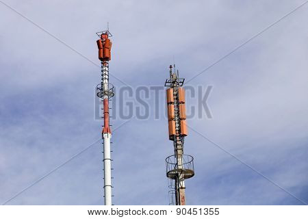 Two towers of communications with different antennas under blue sky.