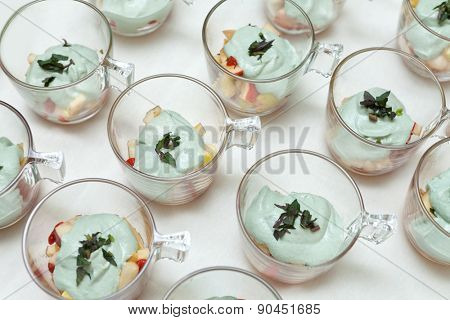 Fruit salad made of apples, pears and lemon juice, topped with whipped cream of indian nuts and spirulina, with mint leaves.