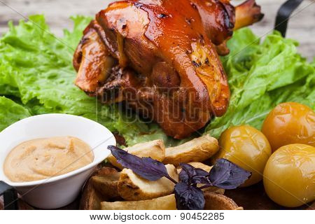 Appetizing roast pork knuckle on cutting board