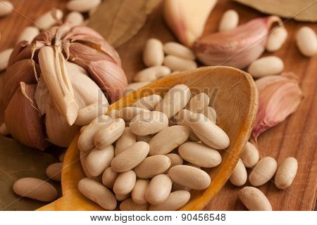 Beans in a wood spoon on natural textured wood background. Natural uncooked raw organic food