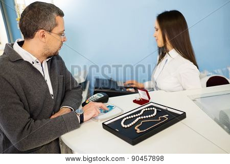 Man paying with credit card in  jewellery shop