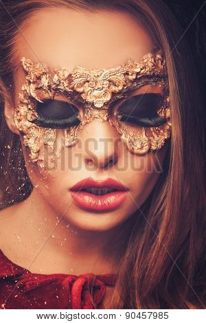 Woman with creative carnival mask on her face falling apart