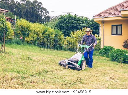 Young man mowing the lawn with lawnmower